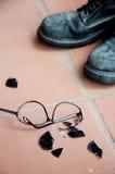Broken Sunglasses and Black Boots. Broken sunglasses and black army boots on clay floor Royalty Free Stock Photo