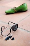 Broken Sunglasses and Green Shoe Stock Photo