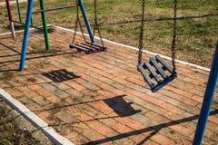 Broken swing. In a school yard Stock Photos