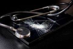 Broken tablet with broken screen and stethoscope in repair. Black table. Black background royalty free stock image