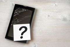 Broken tablet computer with cracked screen and a question mark on wooden background. Copy space stock photo