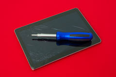 Broken tablet with screwdriver suggesting technology and gadget repair services under warranty Royalty Free Stock Image