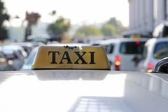 Broken taxi light sign or cab sign in drab yellow color with black text on the car roof at the street blurred background. Myanmar royalty free stock images