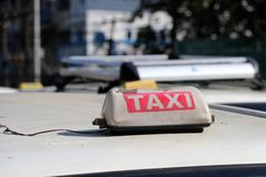 Broken taxi light sign or cab sign in drab white and red color with white text on the car roof at the street. Blurred background, Myanmar royalty free stock images