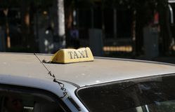 Broken taxi light sign or cab sign in drab yellow color with black text on the car roof at the street blurred background. Myanmar royalty free stock photos
