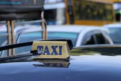 Broken taxi light sign or cab sign in drab yellow color with blue text on the car roof. At the street blurred background, Myanmar royalty free stock photos