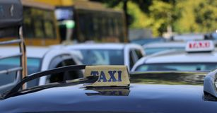 Broken taxi light sign or cab sign in drab yellow color with blue text on the car roof. At the street blurred background, Myanmar stock photo