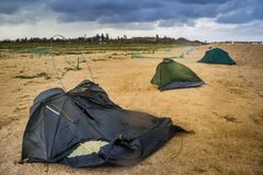 Broken tent at the beach. Blue broken camping tent on the beach at the stormy weather and good tent at back Royalty Free Stock Images