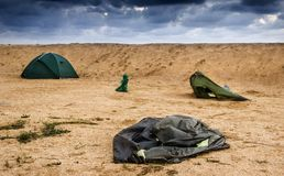 Broken tent at the beach. Blue broken camping tent on the beach at the stormy weather and good tent at back Stock Photo
