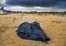 Broken tent at the beach. Blue broken camping tent on the beach at the stormy weather Stock Photography