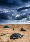 Broken tent at the beach. Blue broken camping tent on the beach at the stormy weather and good tent at back Royalty Free Stock Image