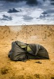 Broken tent at the beach. Brown broken camping tent on the beach at the stormy weather Royalty Free Stock Images