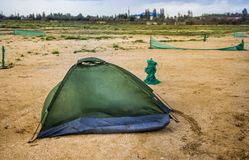 Broken tent at the beach. Green broken camping tent on the beach at the stormy weather Royalty Free Stock Photo