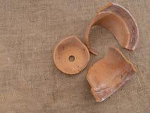 A broken terracotta flowerpot on hessian, top view, frost damage. A broken terracotta flowerpot on hessian, top view, frost damaged stock images