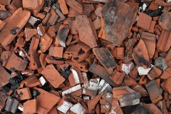 Broken terracotta tiles from burnt roof. Smashed roof tiles, clay red tiles. Roof destrucion. stock photos