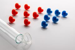 The broken test tube in the foreground and the letters of IVF from red and blue hearts. Concept of unsuccessful in vitro stock image
