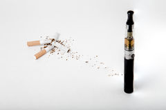 Broken tobacco cigarettes with modern electronic cigarette. Quit smoking, start vaping. Two broken smokes Royalty Free Stock Photo