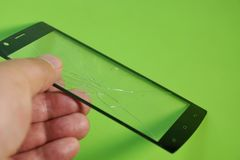 Broken touch screen smartphone in the hand on green background. Repair replacement touchscreen for the phone royalty free stock images