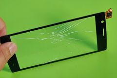 Broken touch screen smartphone in the hand on green background. Repair replacement touchscreen for the phone royalty free stock image