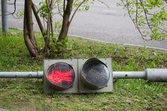 A broken traffic light lies on the sidewalk. Stock Images