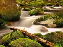 Broken trunk blocked between boulders at stream bank above bright blurred waves. Big mossy stones in clear water of river. Royalty Free Stock Photos