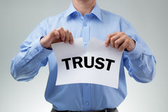 Broken trust. Businessman tearing up sign saying trust concept for infidelity, dishonesty and cheating Stock Photography