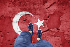Broken Turkey flag with a man. Top view of a man standing on damaged cracked cement floor painted with Turkey flag. Point of view perspective used. Conceptual royalty free stock images
