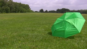 Broken umbrella blown by wind away. Runaway umbrella.  Strong wind in the field blows green parasol away stock footage