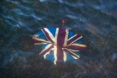Broken umbrella with Union Jack on it, discarded in shallow river.  stock photo