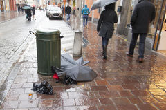Broken umbrellas lie in the street. Rainy day. Royalty Free Stock Photography