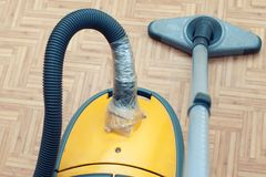 A broken vacuum cleaner. Torn Hose wrapped in duct tape.  royalty free stock photo