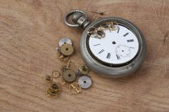 Broken vintage pocket watch on wooden. Background royalty free stock images