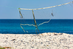 Broken volleyball net hanging on a beach. Blue sea in background Royalty Free Stock Photo