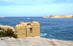Broken wall on the coast of Malta. Rest of broken wall on the coast of Malta, lighthouses on background Royalty Free Stock Image