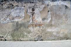 The broken wall near to sidewalk. Stock Photography