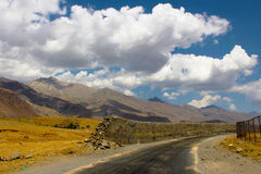 Broken wall on road near Kargil with white clouds. A broken wall on road near Kargil in Kashmir, India. We can see mountains and white clouds in blue sky in Royalty Free Stock Image