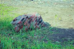 Broken wall stone. In the field grass stock image