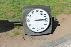 Broken watch dial. The street post with the clock lies on the ground. royalty free stock photos
