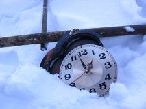 Broken watch lying in the snow thrown the wrong time royalty free stock photo