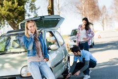 Broken wheel man helping two female friends. Broken wheel men changing tire help two female friends royalty free stock images