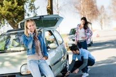 Broken wheel man helping two female friends