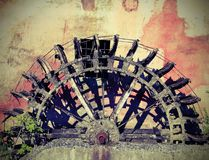 Broken wheel of an old abandoned water mill with vintage effect Royalty Free Stock Images