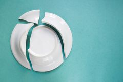 Broken white plate on green background, copy space, top view royalty free stock photos