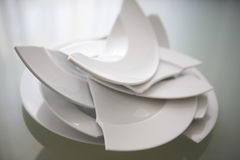 Broken white plates on glass table. Pile of broken white plates on glass table royalty free stock photos