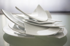 Broken white plates on glass table. Pile of broken white plates on glass table royalty free stock image