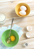 Broken and whole egg in a bowl. On a wooden table Stock Photography