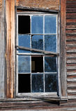 Broken Window. Weathered wood siding and sashes frame a broken and deteriorating 12 pane window Royalty Free Stock Photo