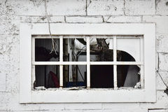 A broken window in an abandoned building by the side of the road in white Stock Photo