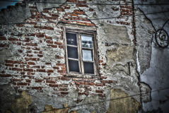 A broken window on an abandoned house. A broken window on a naked brick wall Stock Image