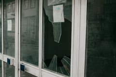 Broken window as a result of an earthquake or vandalism or other negative event. A broken window in a residential building or store as a result of an earthquake stock photos